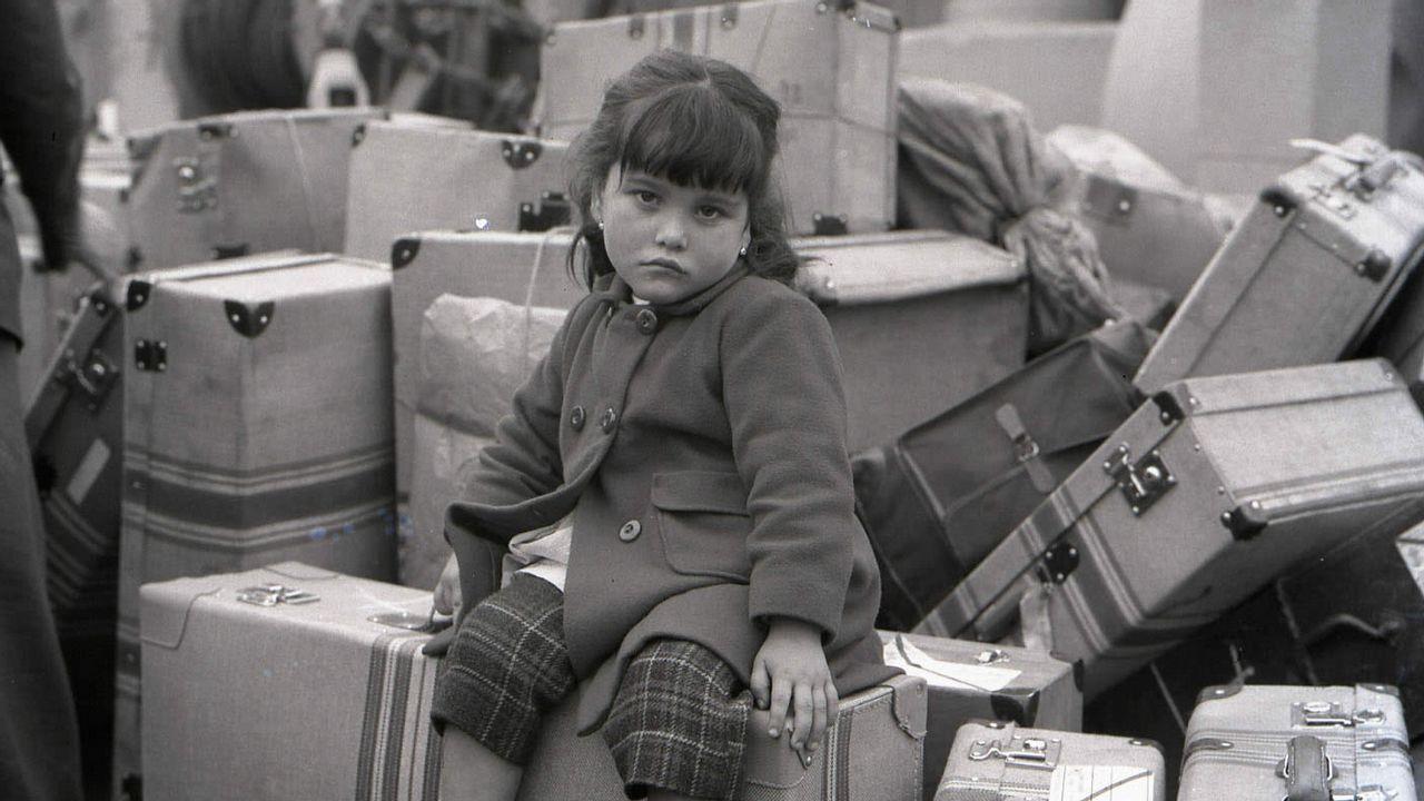 Unha nena agarda pola súa nai sentada nas maletas na Coruña de 1963, nunha das instantáneas da exposición «Os adeuses» que viaxará a Estados Unidos