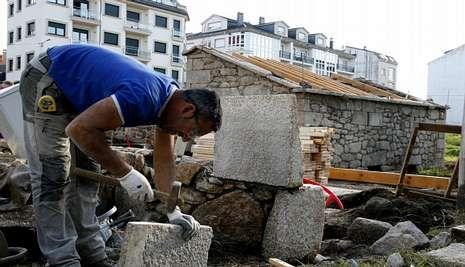 Un cantero trabaja en la restauración del molino ubicado en pleno casco urbano de Vimianzo.