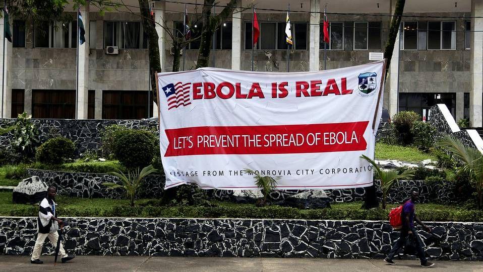 Así es el protocolo ante un caso de ébola.Fotografía de archivo fechada el pasado 31 de julio del 2014 que muestra a varios liberianos caminando frente a un cartel que alerta sobre los peligros del ébola en el Ayuntamiento de Monrovia (Liberia)