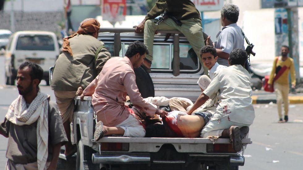 Civiles evacúan a los heridos en los bombardeos saudíes sobre el puerto de Adén.