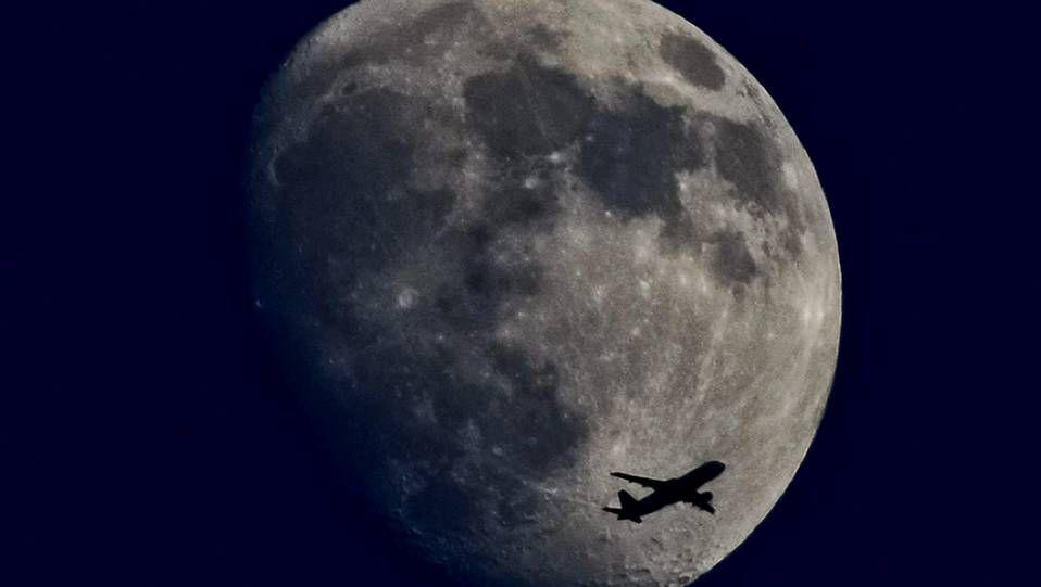 Un avión vuela con la luna creciente de fondo en Alemania.