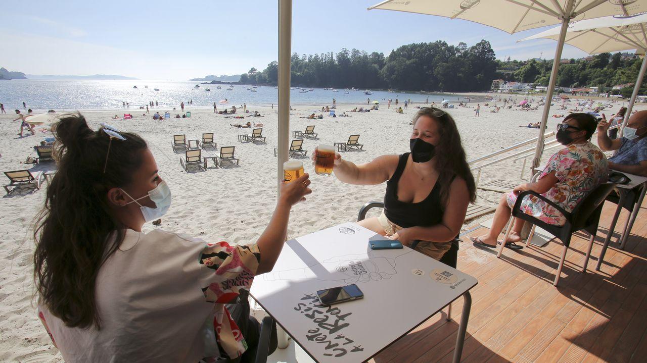 Dos clientas brindan por el verano en la terraza del chiringuito Argentina de Cabanas
