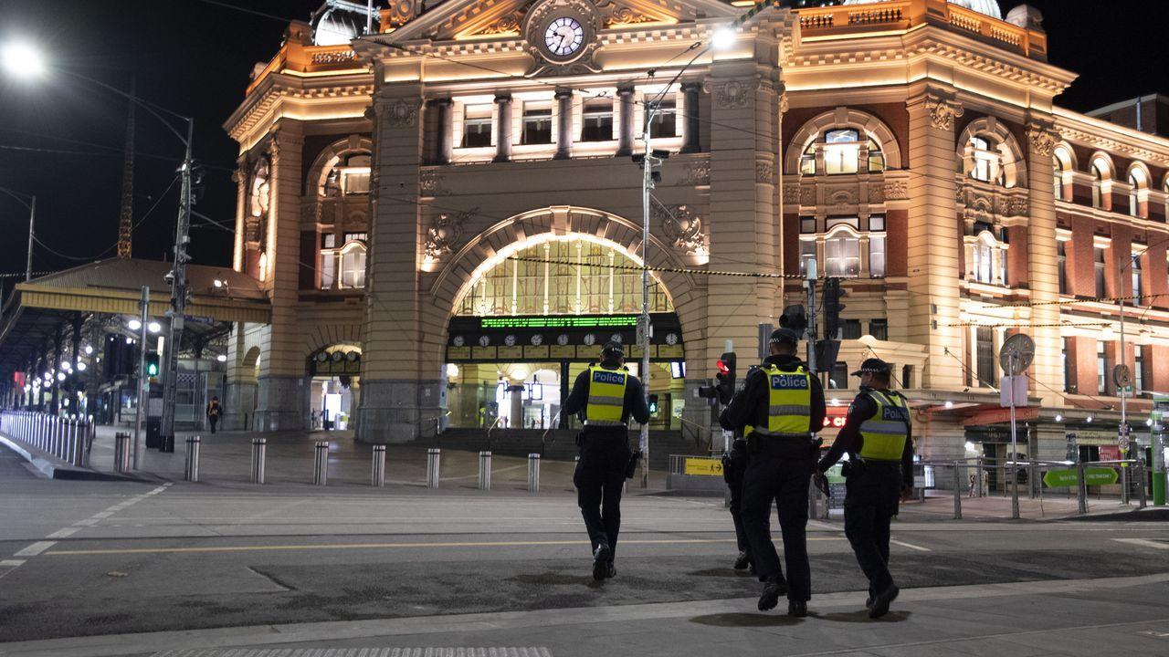 Policías al frente de la Estación de Flinders Street en Melbourne, vigilando el toque de queda durante la madrugada