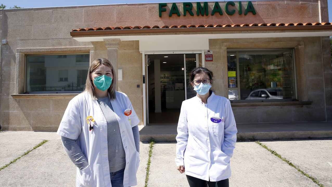 Ana Romero y Margarita Goldar posan delante de la farmacia, que ayer reabrió sus puertas