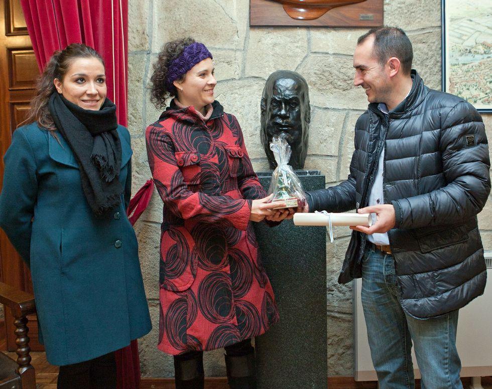 El alcalde le hace entrega del premio a la autora galardonada.