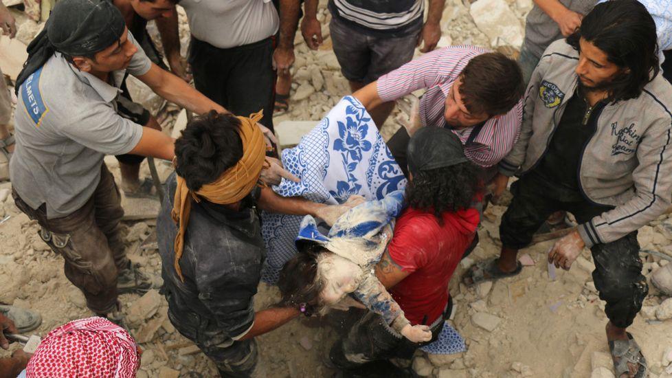 Vecinos se pasan el cuerpo de una niña sacada de los escombros de un edificio bombardeado en el barrio de Al Marja.