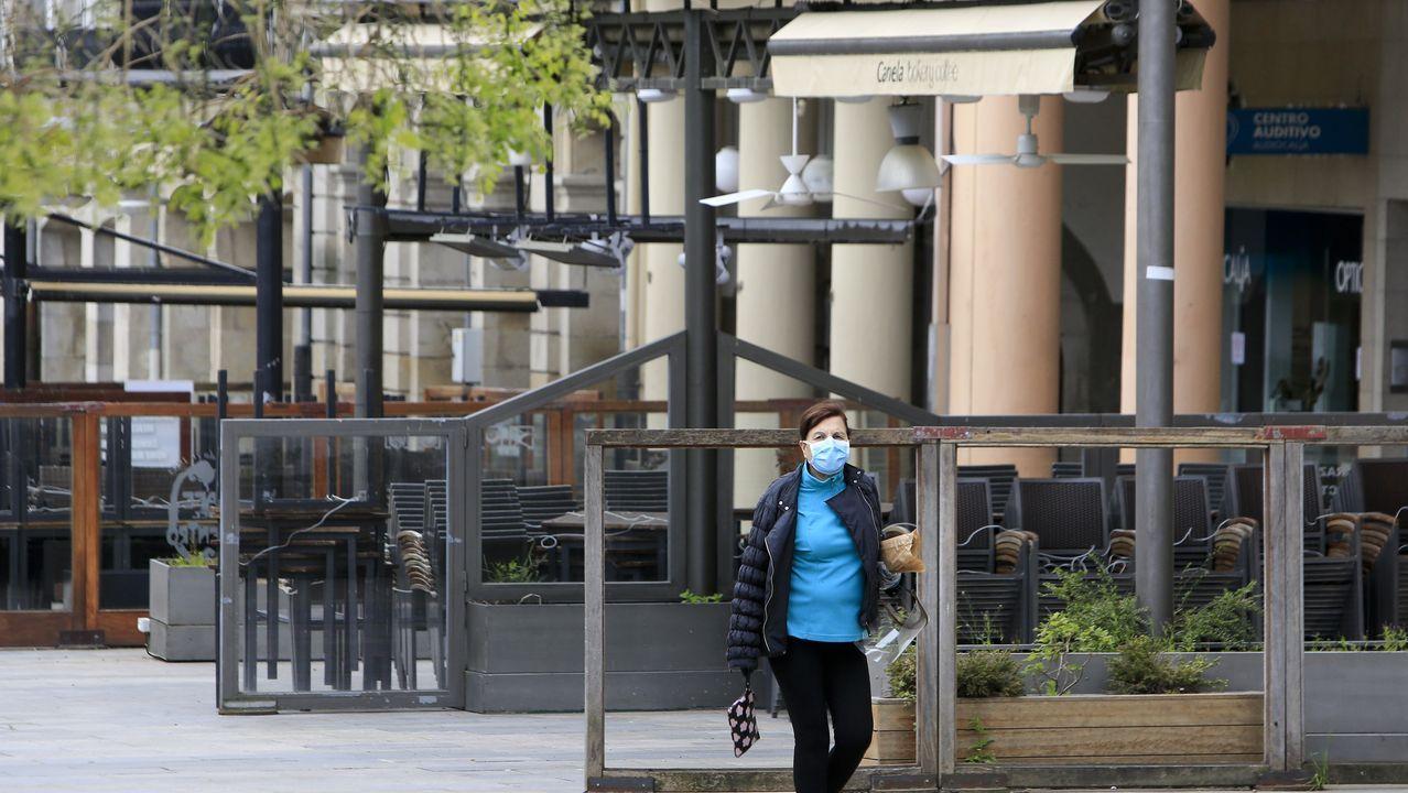 Un hombre con mascarilla pasea con su hija frente a la puerta del parador de turismo de Monforte, cerrado por la crisis del coronavirus