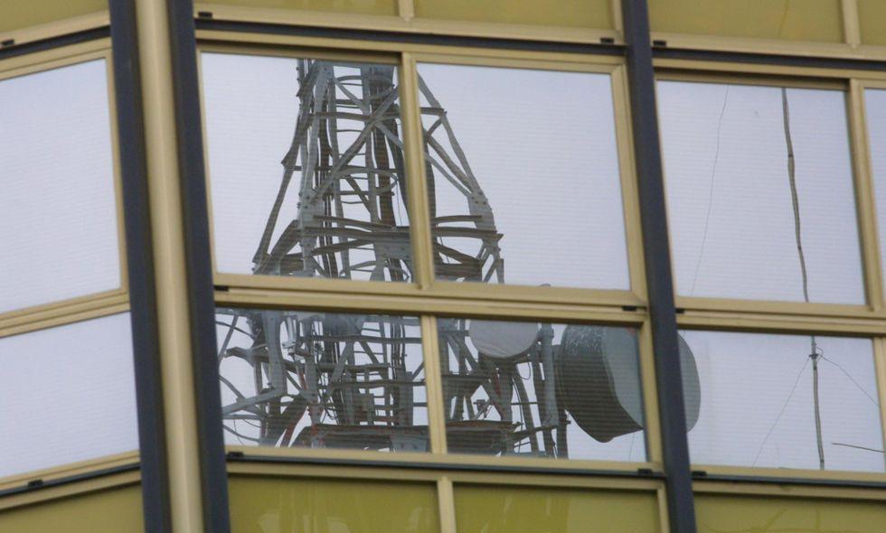Antena de telefonía móvil reflejada en la fachada de un edificio del casco urbano de Lalín.
