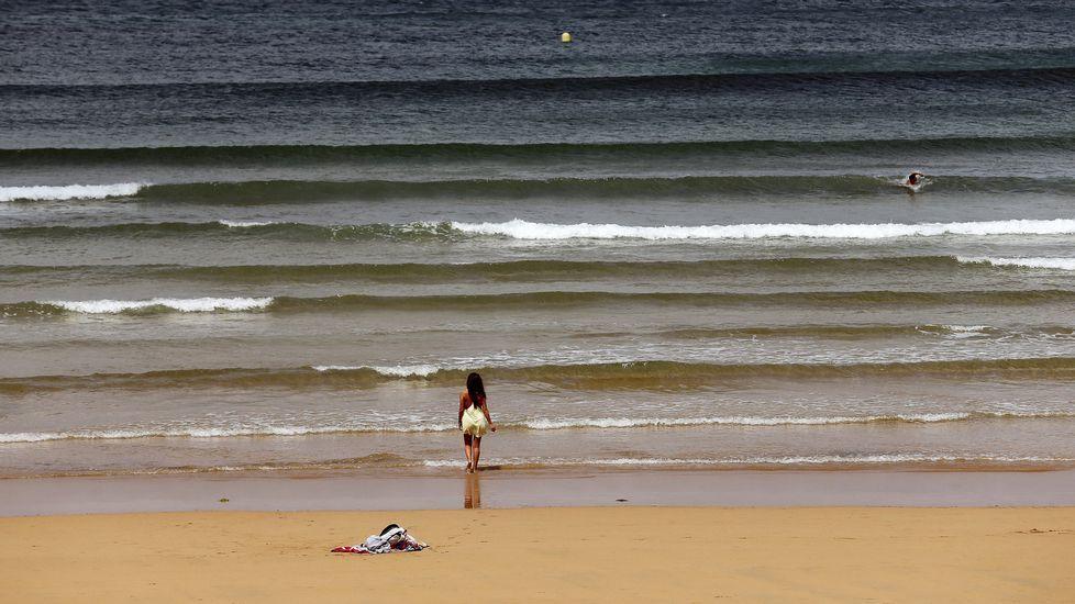 un alumno en un aula, clase, vacía.Cielo nublado hoy sobre la playa de San Lorenzo de Gijón.