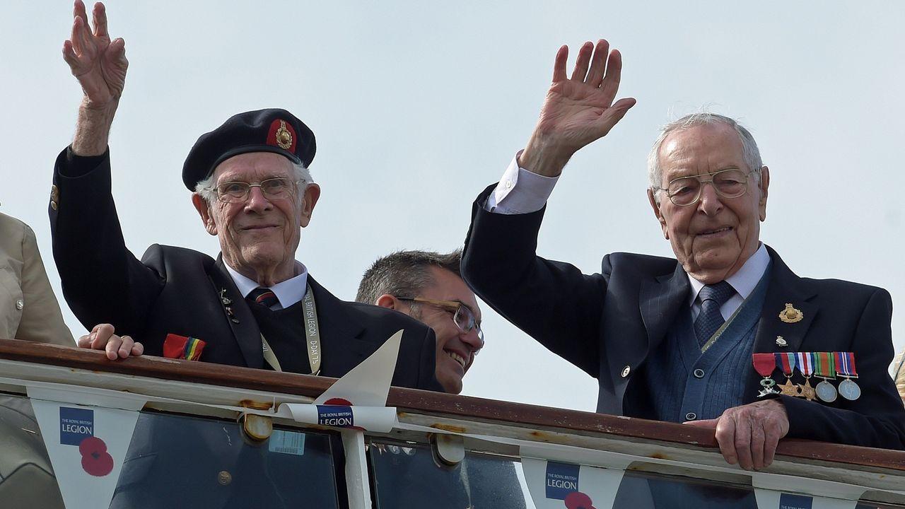 Veteranos británicos de la Segunda Guerra Mundial saludan a su llegada a bordo del barco MV Boudicca al Puerto de Poole