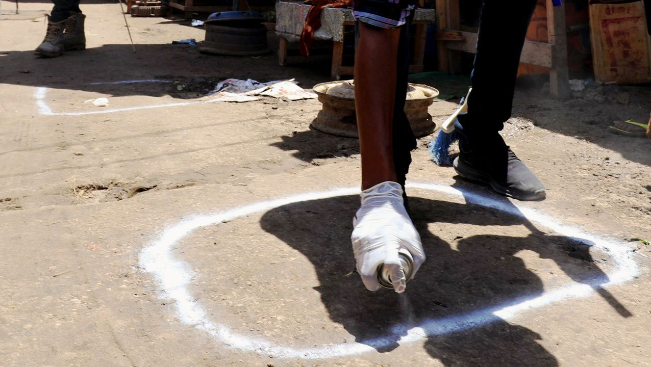 Un trabajador sanitario pinta en el suelo de una localidad de Somalia zonas para mantener la distancia social