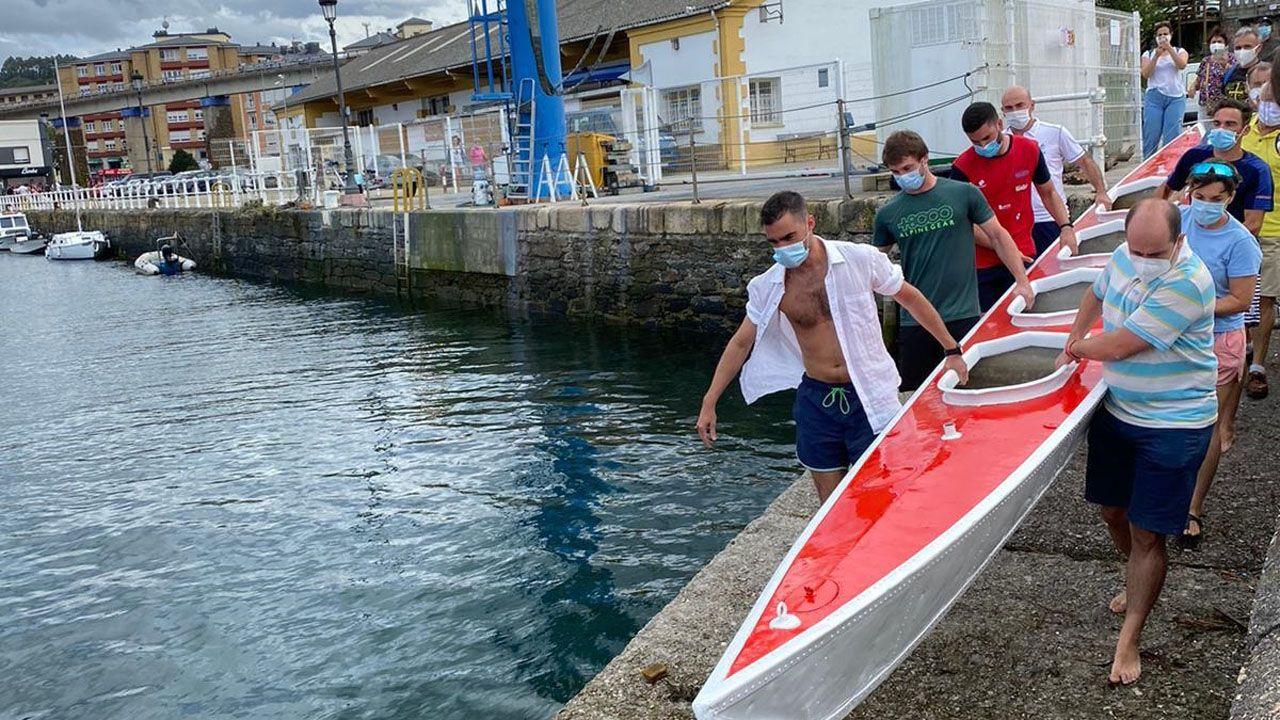 Varias personas traslsadan la canoa Virgen de la Barca hacia la ría de Navia