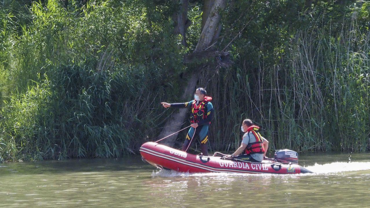 El jefe de Rastreo forestal y rastreador profesional, Fernando Gómez (sentado) y un agente del Seprona de la Guardia Civil, en una lancha durante las tareas de búsqueda del cocodrilo que fue avistado el pasado sábado en Pesqueruela