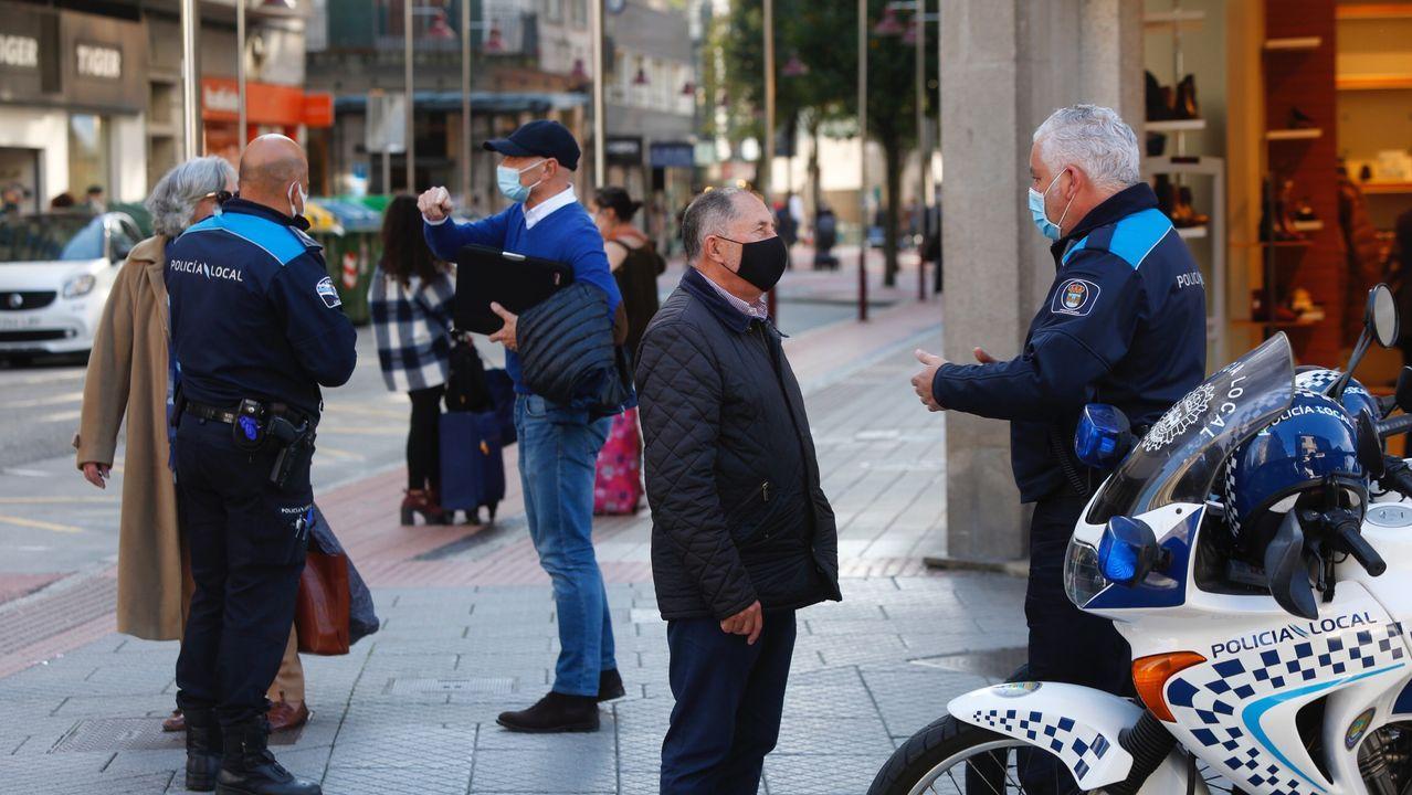 Policías locales, informando de las nuevas restricciones a varios viandantes