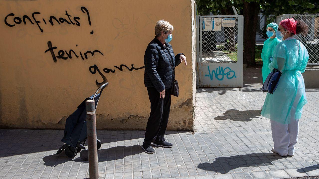 España registra 87 nuevos muertos por coronavirus, la cifra más baja en dos meses.Dos enfermeras de atención domiciliaria charlan con una vecina en el barcelonés barrio del Raval