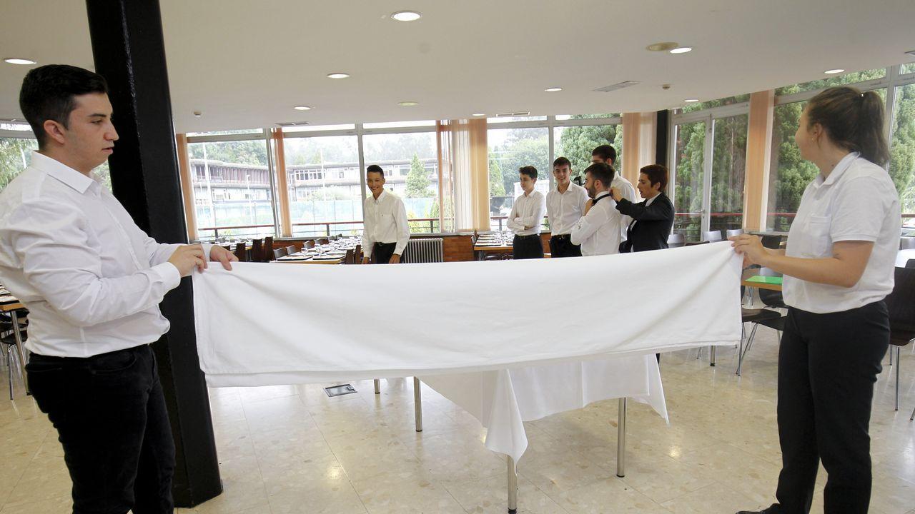 Mientras la profesora le coloca la pajarita a un alumno, dos compañeros doblan un mantel totalmente acompasados