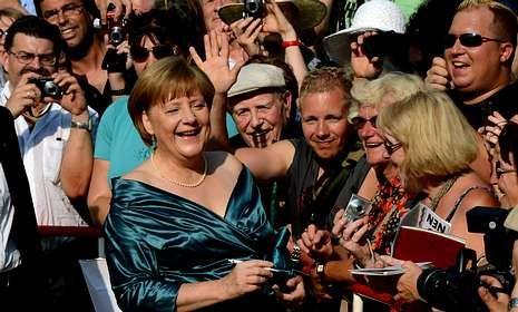 Merkel, de vacaciones, firmó ayer autógrafos en la inauguración del festival de Bayreuth.