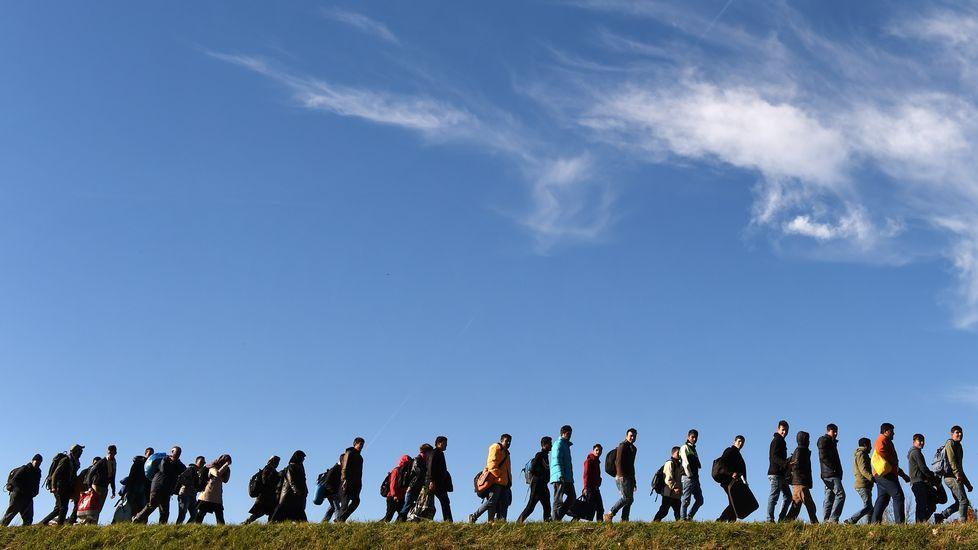 Emigrantes caminan hacia un primer punto de registro de la policía federal alemana después de cruzar la frontera austro-alemana en la pequeña localidad bávara de Simbach, el sur de Alemania