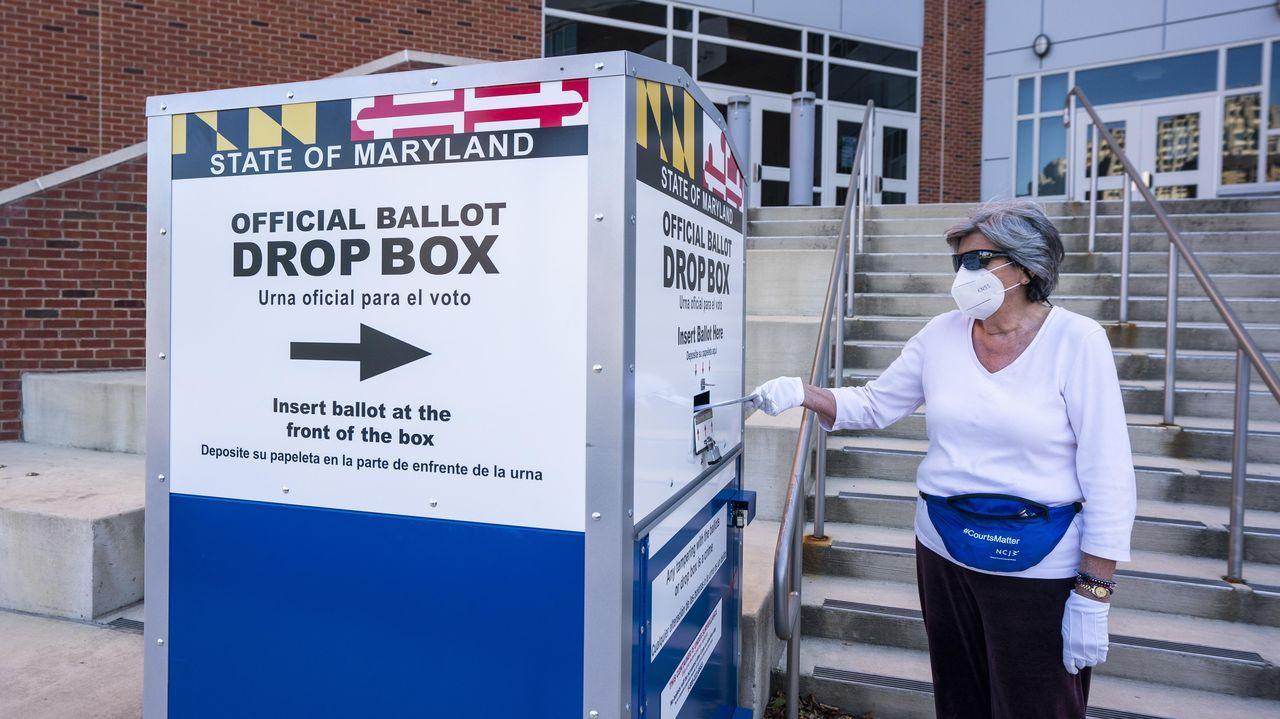 Una mujer depostia su voto anticipado en una oficina electoral de Maryland