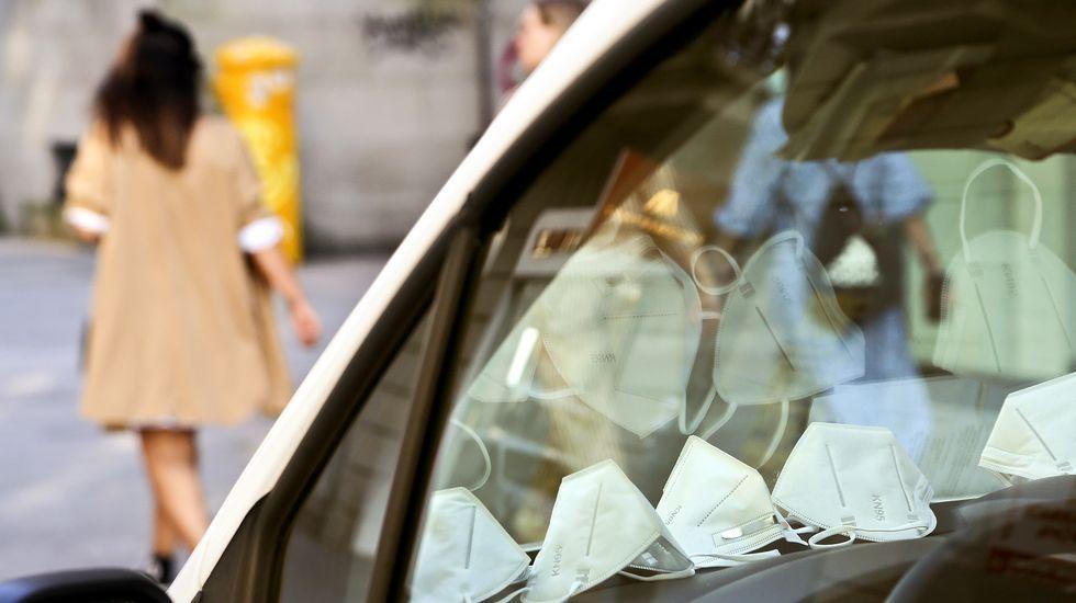 Mascarillas acumuladas en el salpicadero de una furgoneta en el centro de Vigo