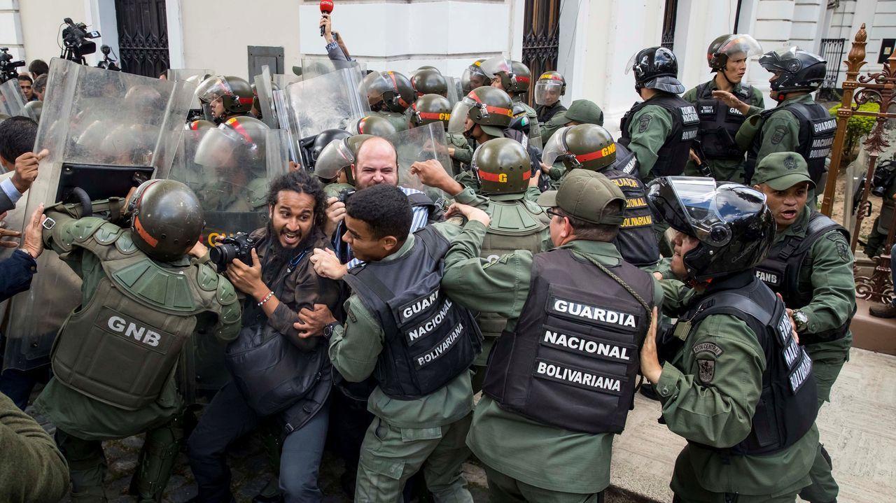 Miembros de la Guardia Nacional Bolivariana (GNB) forcejean con periodistas que intentan entrar al Palacio Federal Legislativo