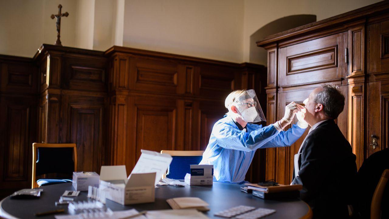Un médico le hace la prueba del coronavirus al obispo Christian Staeblein en la catedral de Berlín antes de los oficios del domingo de Resurrección