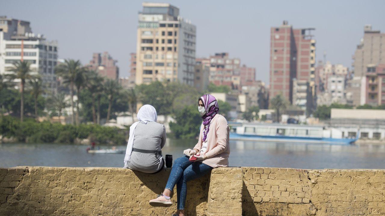 Una niña con mascarilla protectora se sienta frente al río Nilo en El Cairo