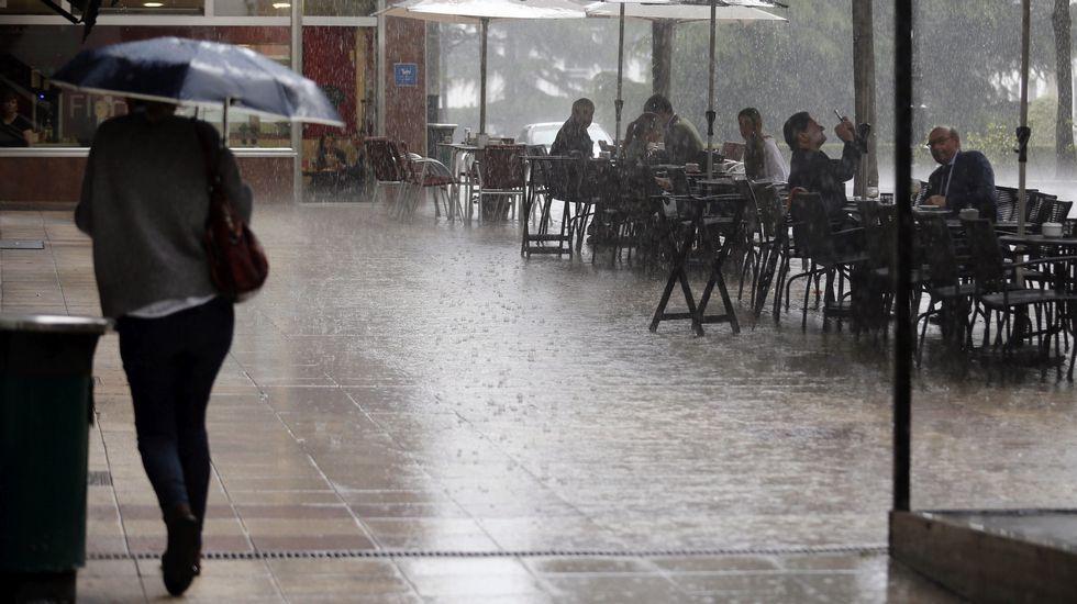El otoño será más cálido de lo normal en Galicia.Una intensa lluvia en las calles de Oviedo