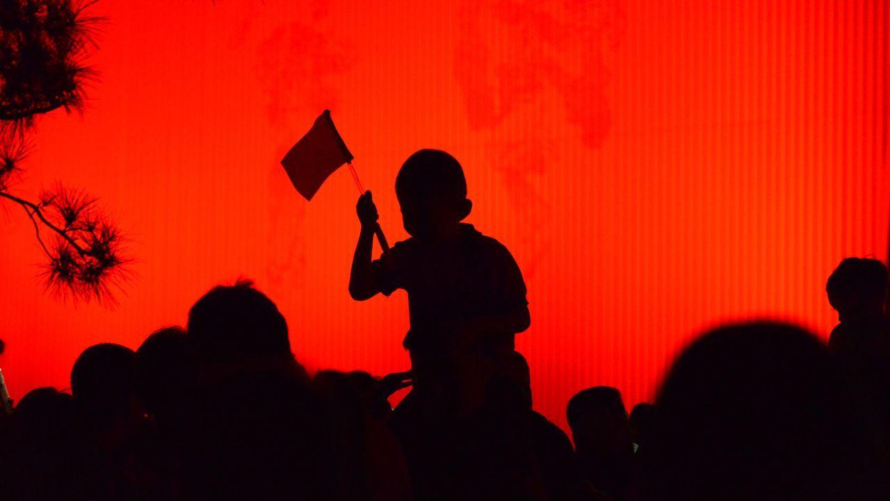 Un niño sujeta una bandera en la plaza de Tiananmen en los actos previos al 70 aniversario