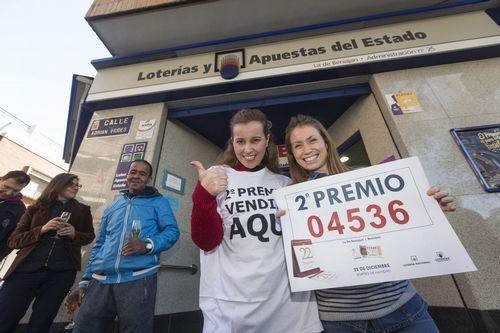 La dueña de la Administración de Lotería Nº 25 de Beniaján, Elena Turpín, acompañada de la vendedora María García, posan con un cartel que anucia la venta del segundo premio del sorteo de Navidad, el número 04.536