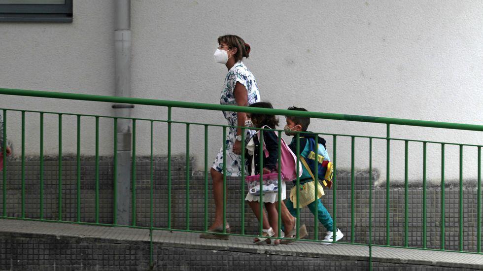 La directora del Colexio Novo de Monforte acompaña a la entrada de su clase a dos niños de educación infantil