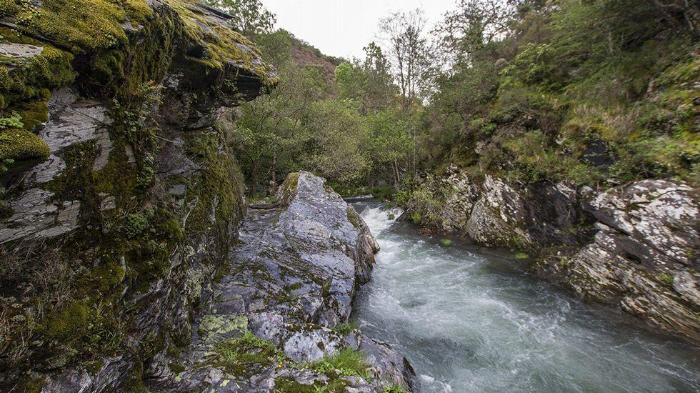 El antiguo canal minero tallado en la roca viva discurre por la margen izquierda del río (a la izquierda en la imagen)