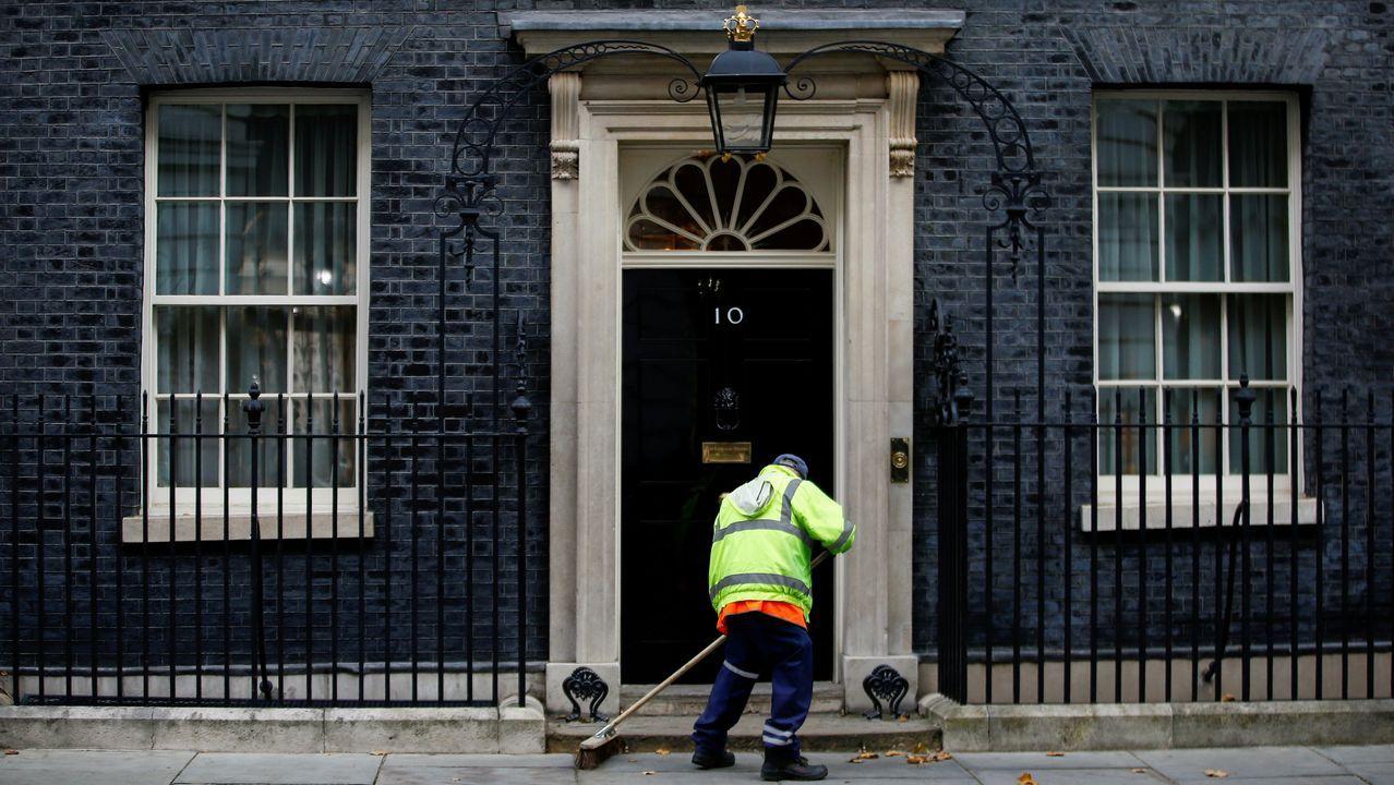 Un operario limpia la acera del número 10 de Downing Street
