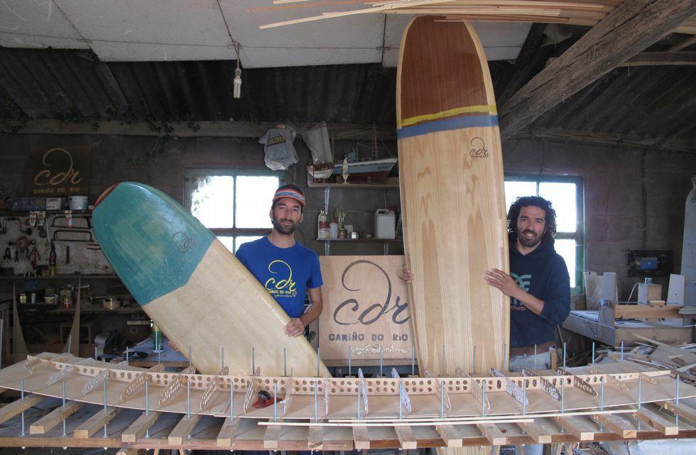 En primer término se ve el esqueleto de una de las tablas que elaboran en Camiño do Río. Pichi y Trigo posan con otras ya terminadas.