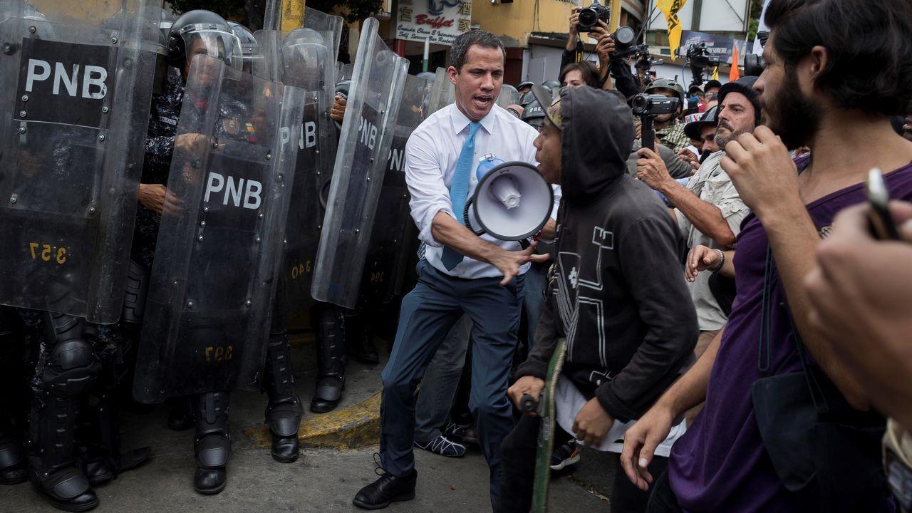 Juan Guaidó junto a otros manifestantes huyen de los gases lacrimógenos arrojados por la Policía Nacional Bolivariana para disolver la marcha convocada por la oposición