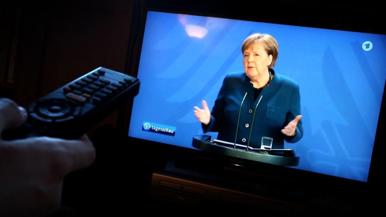 La pandemia en el mundo.Un hombre viendo el discurso de Angela Merkel con motivo de la pandemia