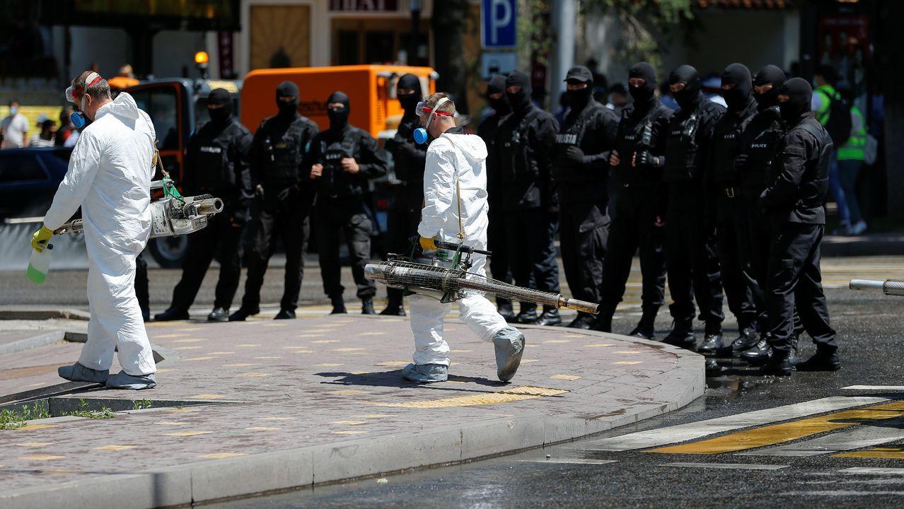 Trabajadores con equipos de desinfección se dirigen a un edificio mientras la policía se prepara para supervisar una manifestación en Kazajistán