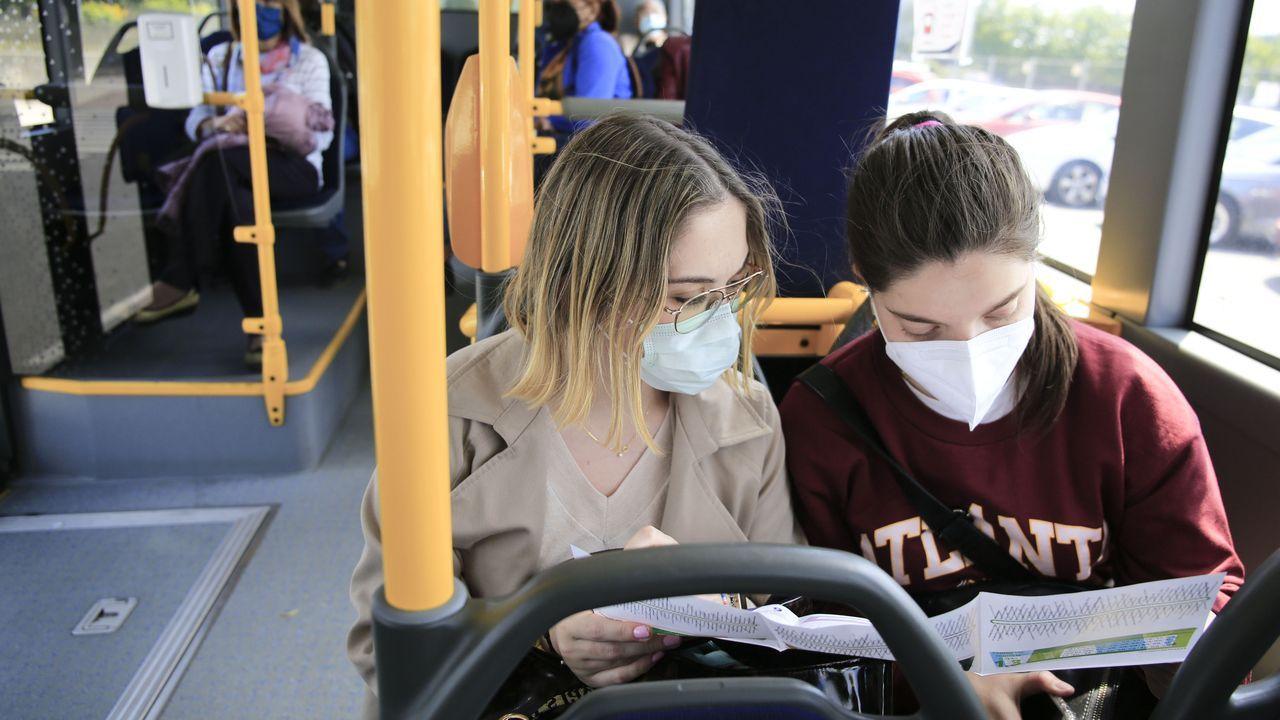 Dos chicas miran con atención las nuevas líneas de bus