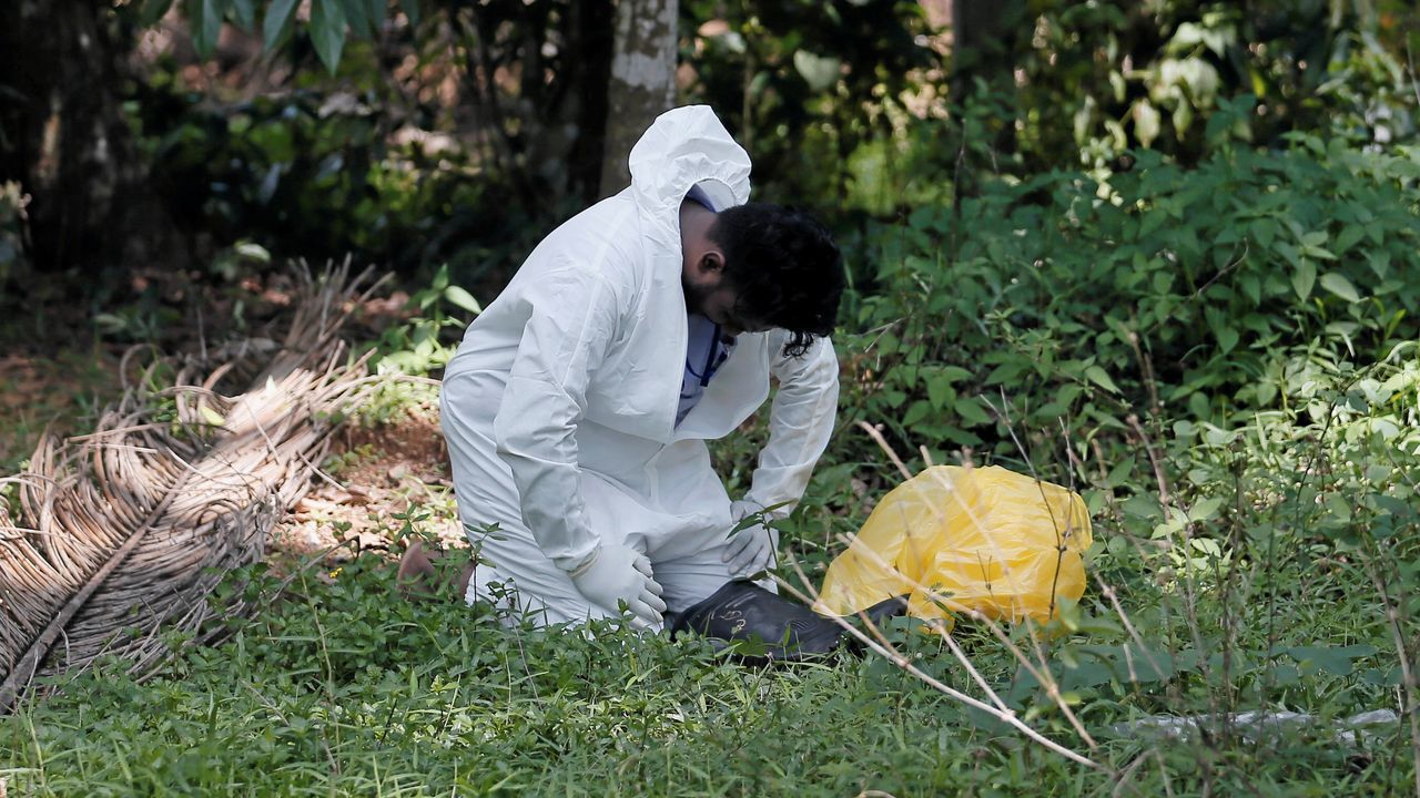 Un funcionario de salud acaba en el suelo mientras recolectaba muestras de los aldeanos durante el toque de queda, en Colombo, Sri Lanka