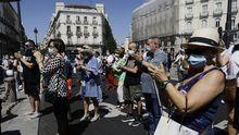 Transeúntes aplauden al finalizar el minuto de silencio en memoria por los fallecidos por el covid-19 en la sede de la Comunidad de Madrid