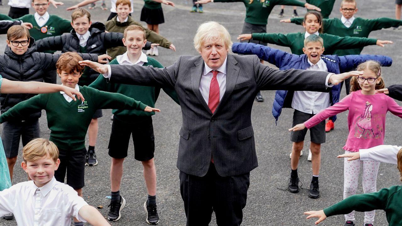 Boris Johnson visitó ayer una escuela donde posó con varios alumnos con los brazos abiertos, una forma de calcular la distancia social
