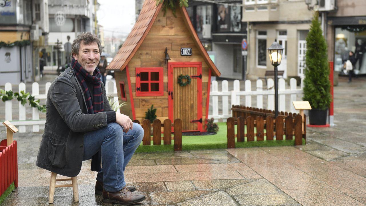 Luis Iglesias a la puerta de su creación, una casa encantada en la aldea navideña lalinense.