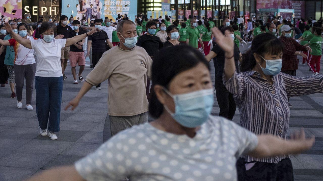 Gente con máscaras practicando deporte, ayer, en una calle de Pekín