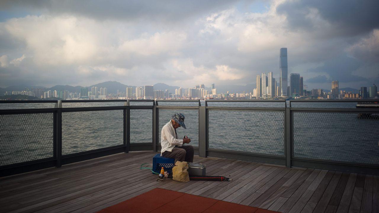 Un anciano prepara su material de pesca en un muelle del puerto Victoria de Hong Kong's