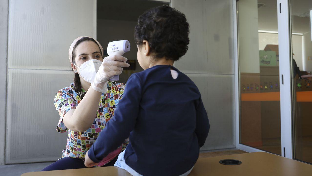 Una monitoria le toma la temperatura a un pequeño en la escuela de Fontiñas, en Santiago