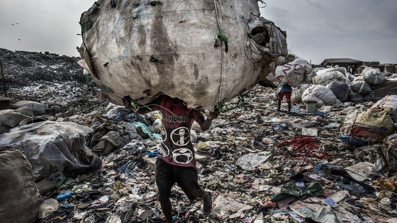 Fotografía cedida por la organización World Press Photo que muestra la imagen captada por el fotógrafo Kadir van Lohuizen, ganador del primer premio de la categoría «Environment - Stories». La foto muestra a un hombre mientras carga un enorme lomo de botellas recogidas para su reciclaje en el vertedero de Olusosun en Lagos, Nigeria, el 21 de enero del 2017
