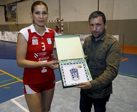 Verónica Contreras recibe una placa de su pareja y presidente de A Pinguela, Mareque.