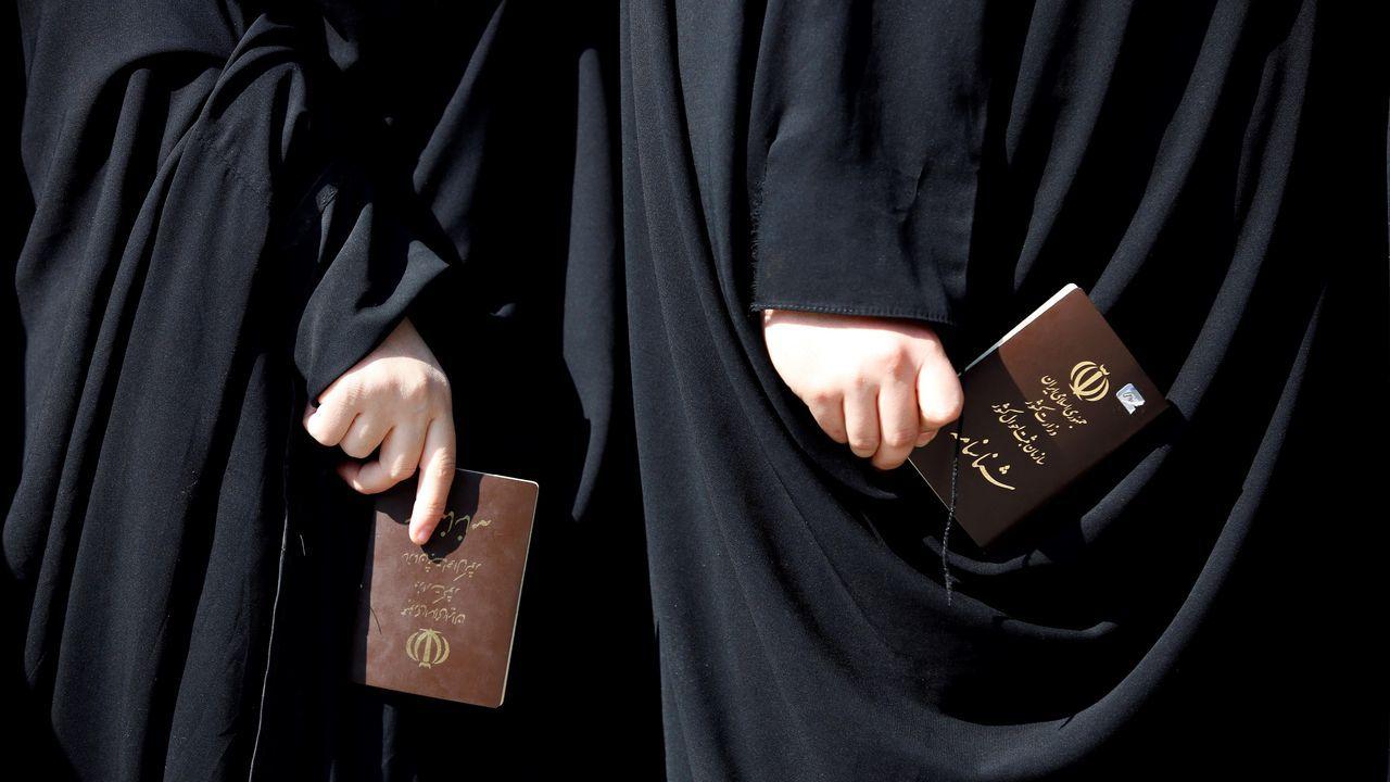 Dos mujeres sostienen sus documentos de identidad en la cola de un colegio electoral antes de efectuar su voto el viernes