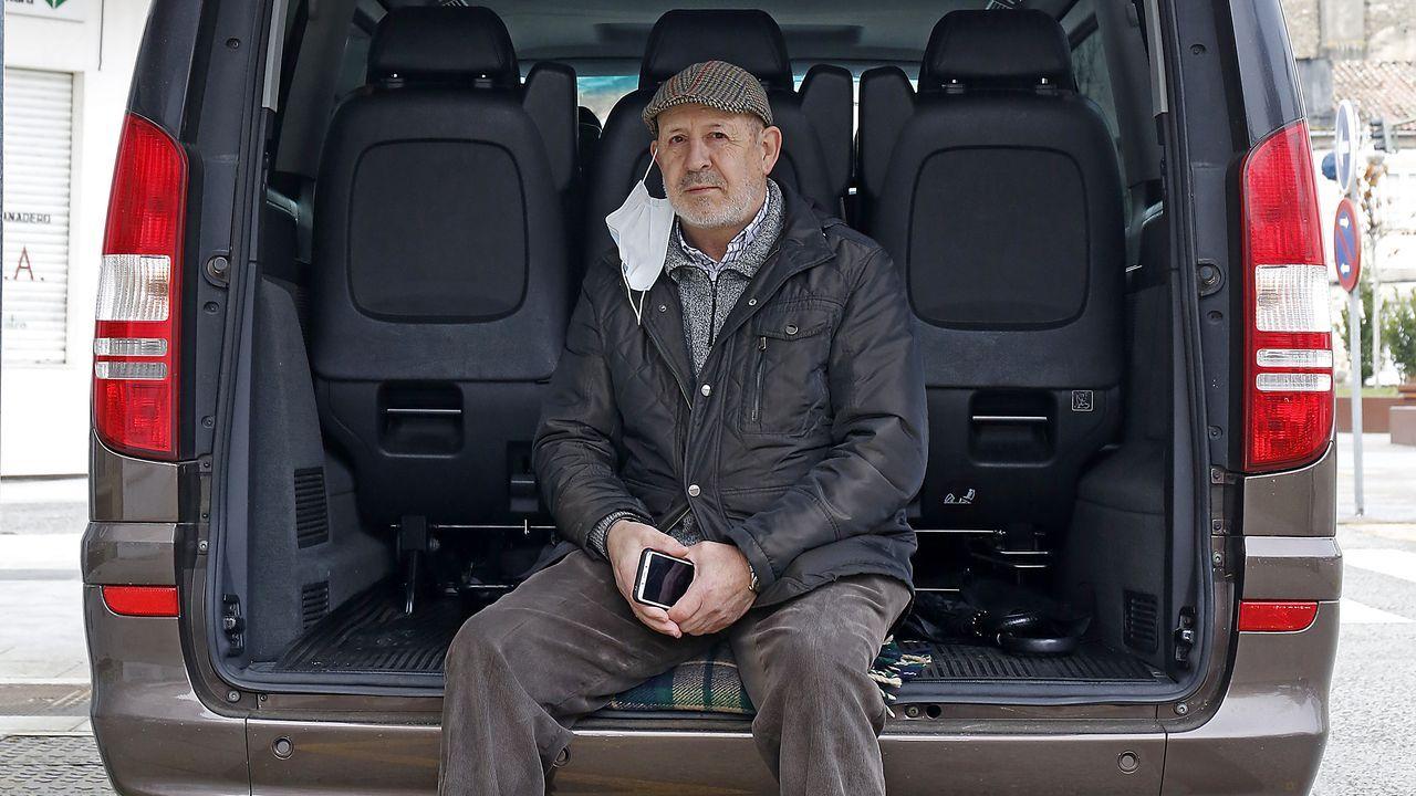 José Luis, propietario de una empresa que realiza excursiones y transporta mochilas, sentado sobre su taxi en Melide