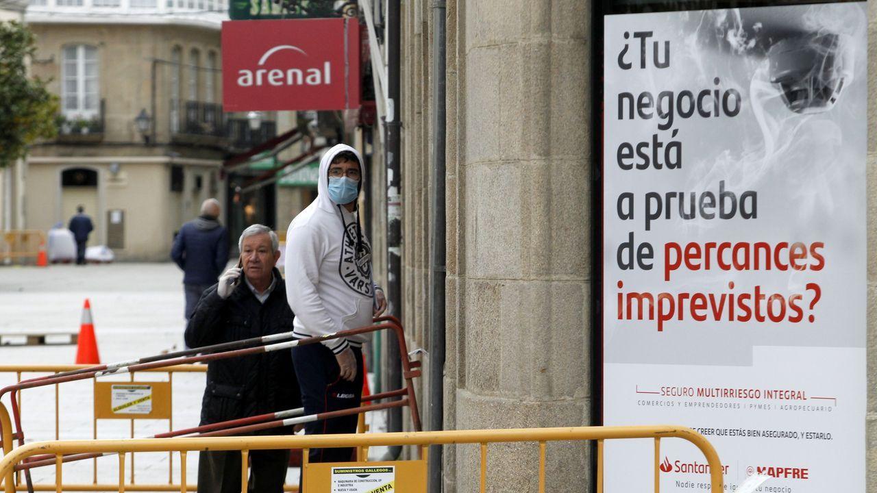 Clientes en la puerta de un banco en la calle Cardenal, en la que casi todos los negocios están cerrados